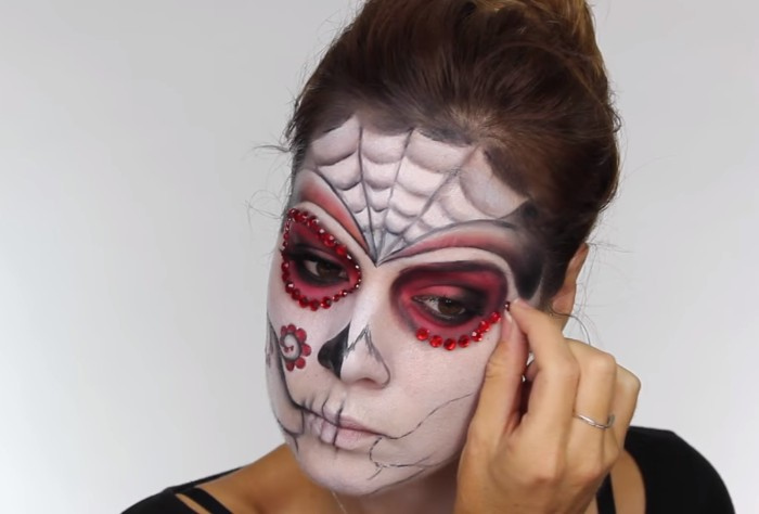 sticking red rhinestones, around the eyes of a young woman, wearing white and black, and pink sugar skull makeup, skeleton face paint, with floral motifs