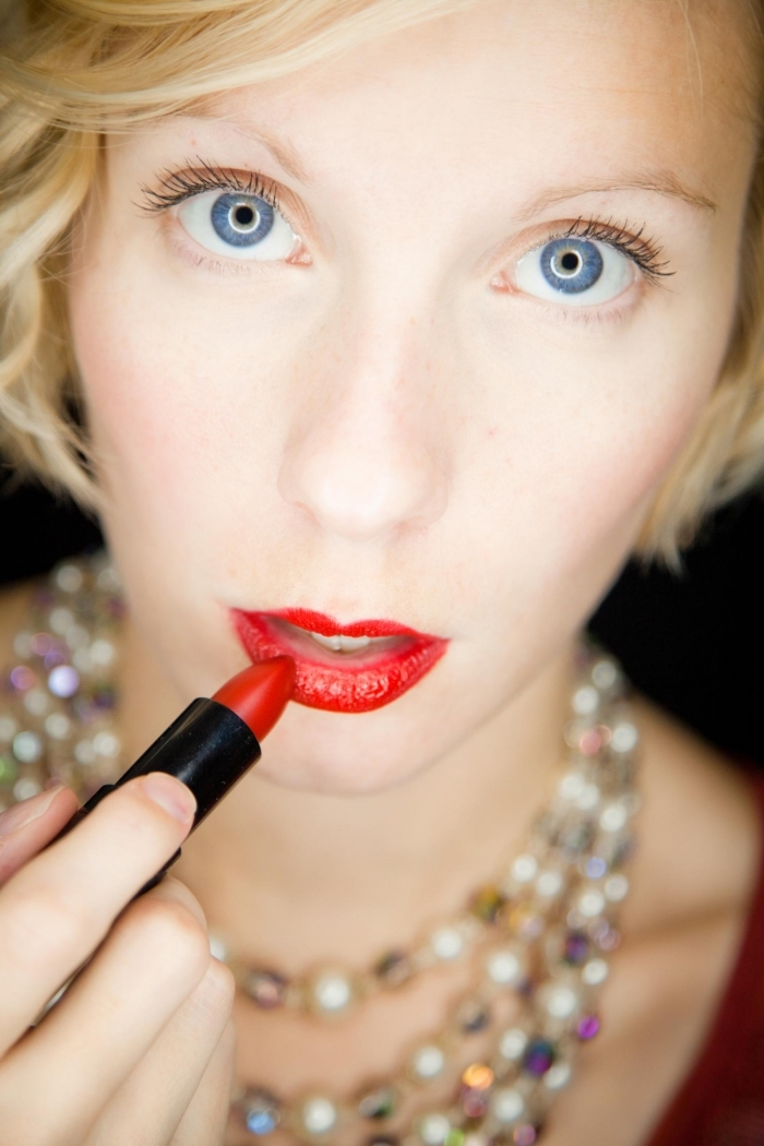 multicolored beaded necklaces, worn by a pale blonde woman, applying red lipstick, while looking at the camera