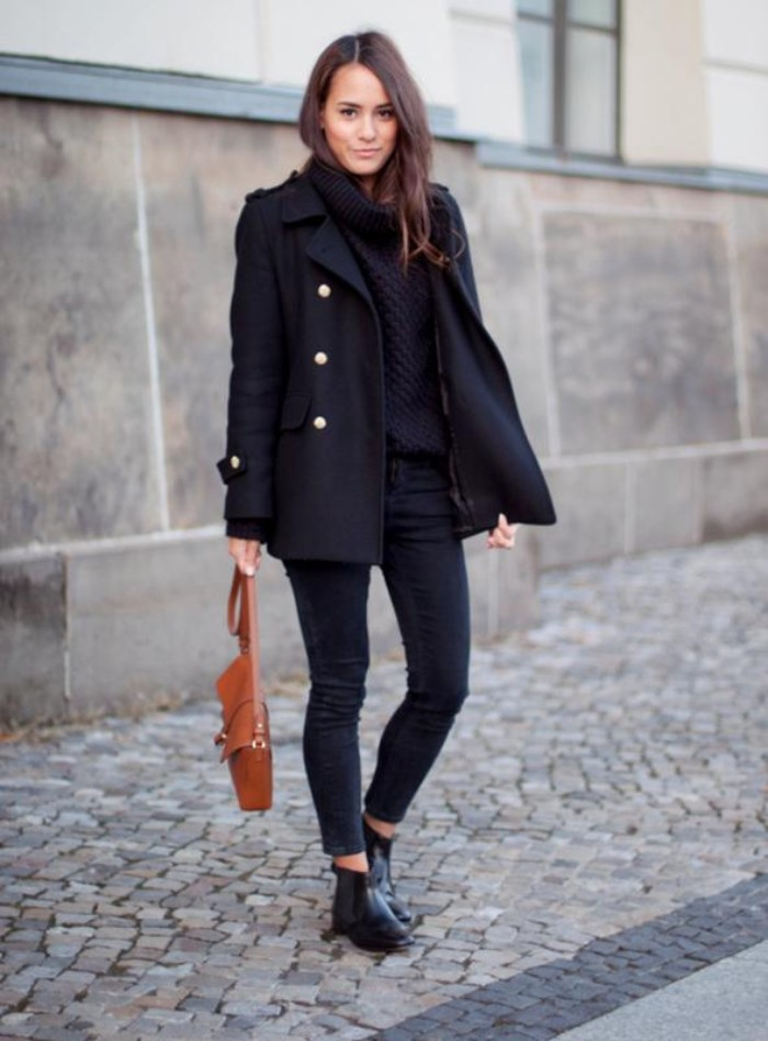 military woolen coat in black, worn by a smiling, young brunette woman, in dark grey skinny jeans