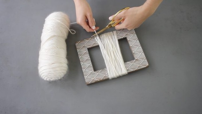 yarn in white, wrapped around a picture frame, room makeover tutorial, one hand holding the end of the yarn, while another is cutting it off with scissors