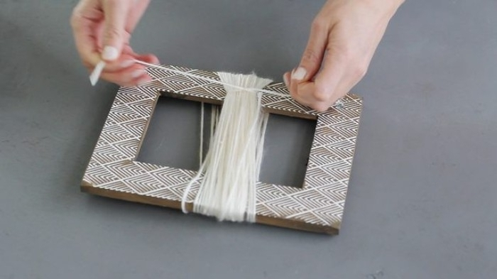 picture frame with white yarn wrapped around it, room makeover tutorial, two hands tying a piece of the same yarn, across the wrapped yarn