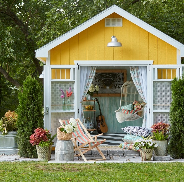 she shed in yellow and white, with open doors, revealing a swing, an acounstic guitar, and other items inside
