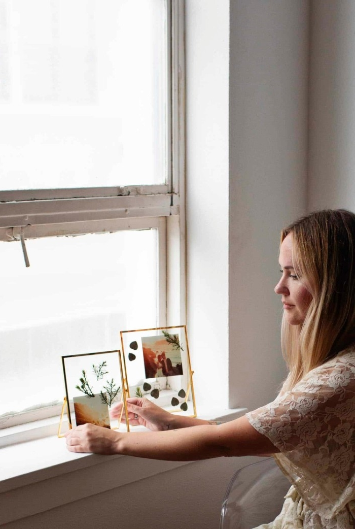blonde woman in a cream lace top, placing a framed artwork, with dried plants and a photo, on a windowsill, dorm wall décor, for the new academic year
