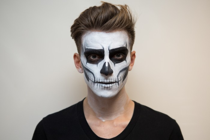 halloween face paint ideas for adults, completed skeleton face paint, worn by a young man, in a black t-shirt