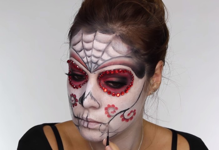 completing a floral motif in red and black, on the face of a young woman, with sugar skull, halloween face paint