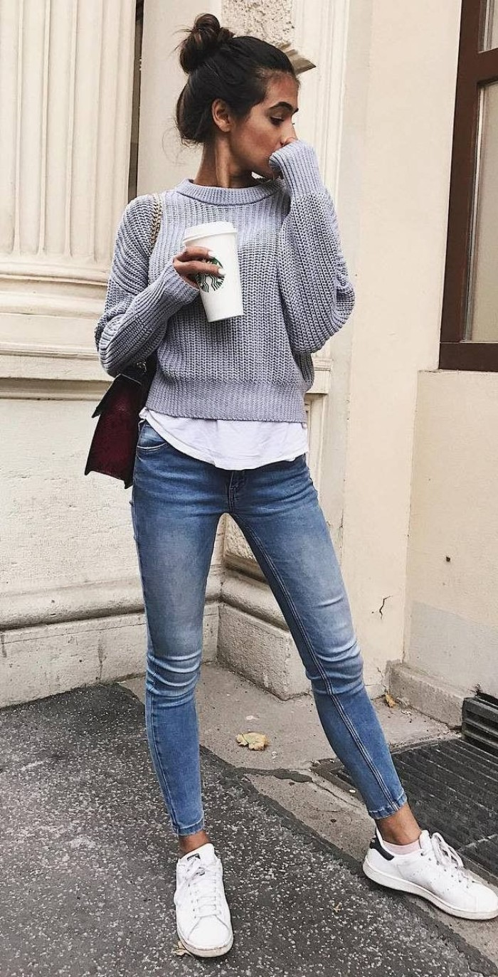top knot worn by a brunette, slim young woman, dressed in blue skinny jeans, with a white shirt, and a pale grey sweater