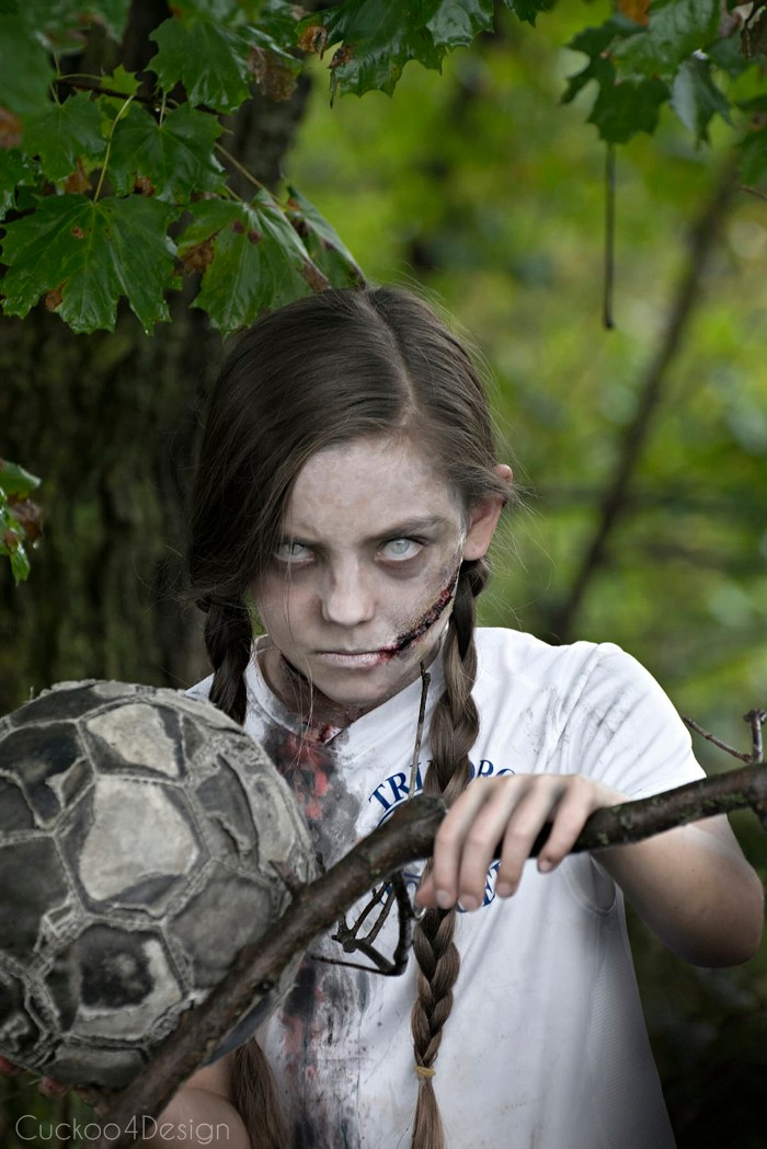 child with long brown pigtails, wearing scary face paint, resembling a zombie, and holding an old football