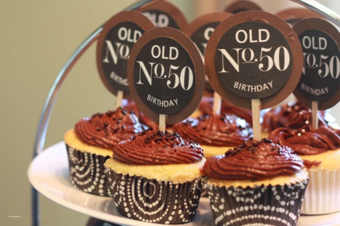 several cupcakes with chocolate frosting, decorated with round toppers, reading old No 50 birthday, in dark brown and white wrappers