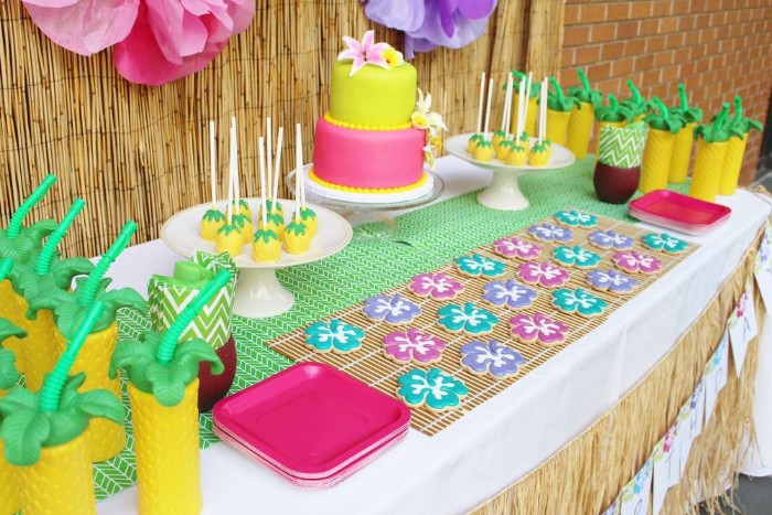 lime green and hot pink cake, decorated with realistic lilies, made from fondant, on a colorful table, with flower-shaped cookies, drinks and sweets shaped like pineapples, 50th birthday colors, hawaiian-themed bash