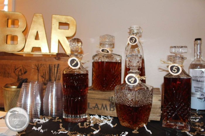 five numbered ornamental glass bottles, each containing a different kind of whiskey, placed on a table, near plastic cups, small decorative wooden crates, and a gold ornament shaped like the word bar, 50th birthday party ideas, whiskey tasting experience