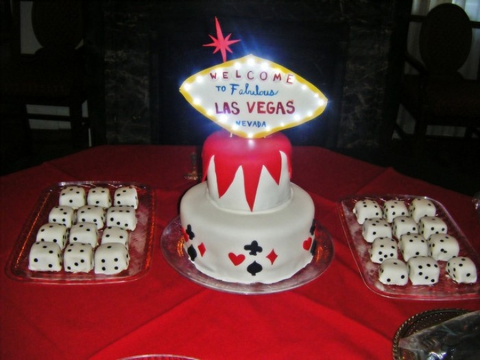 las vegas themed party, two glass trays filled with cube-shaped cakes, decorated to look like dice, birthday cake with glowing topper, shaped like the las vegas sign, 50th birthday party ideas for men