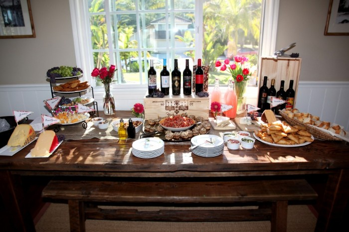 sunlit vintage wooden table, with several bottles of wine, cheese and different snacks, 50th birthday party ideas, plates and cutlery and flowers