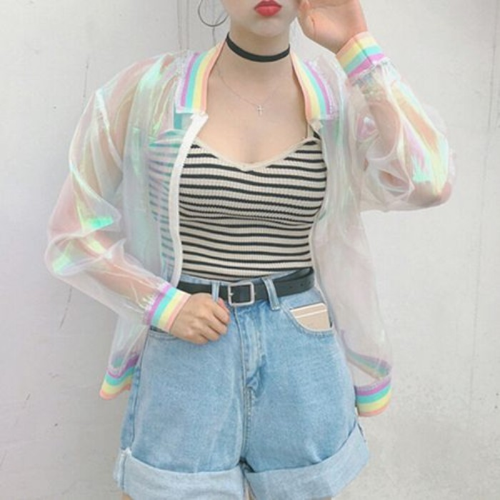 iridescent transparent baseball jacket, with pastel rainbow details, worn over a striped black and white tank top, and pale blue, acid wash high wasited denim shorts, 90s and 80s grunge inspirations