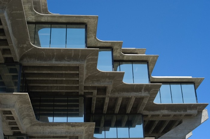 brutalist architecture, the geisel library, university of san diego, angular grey concrete building, with multiple large reflective windows