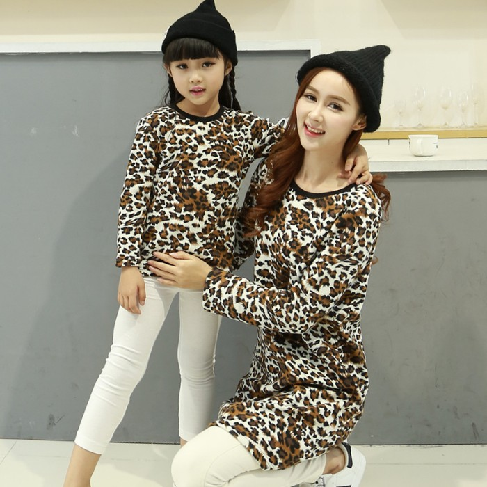 leopard print tops, in white and black and brown, worn with white leggings, and black hats, by a smiling mother, and her young daughter