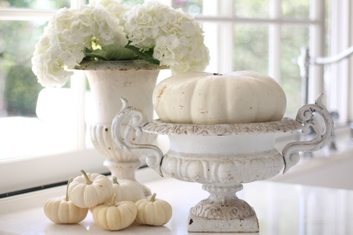 vases in antique style, with chipping white paint, one contains a white pumpkin, and the other - a bouquet of white hydrangeas, five small white pumpkins nearby