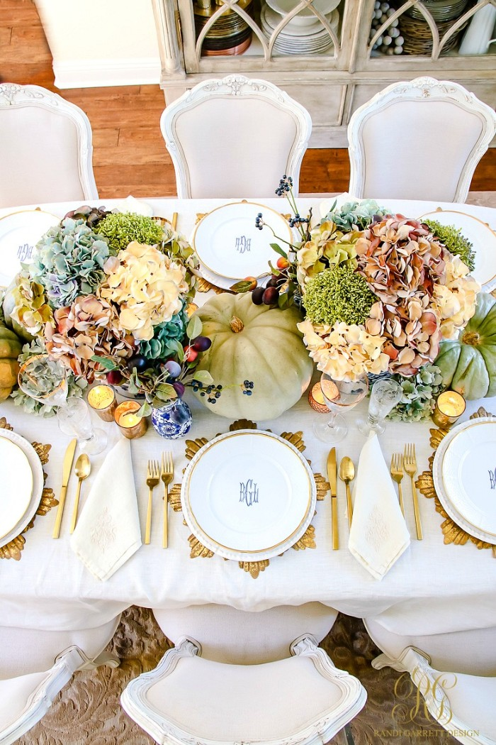 hydrangeas in different colors, accompanied by other plants, in two bouquets, placed on a table, set for a festive meal, cheap centerpiece ideas, pumpkins and lit candles, gold-rimmed plates and gold cutlery