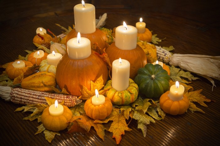 lit candles in different sizes, placed inside pumpkins, in different colors and sizes, orange and dark green, yellow with stripes, dried fall leaves, and ears of corn