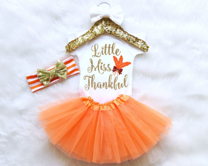 little miss thankful, written in gold, on a white onesie, with orange and brown motifs, tutu skirt in orange, and a white and orange striped headband, with a sparkly gold bow, baby girl thanksgiving outfit