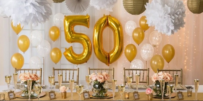 yellow and white balloons, near a table set up for a festive meal, paper decorations and lanterns, two large metallic gold balloons, shaped like the numbers 5 and 0