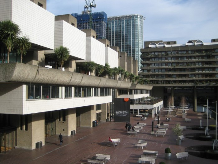 yard of the barbican centre, in london england, multiple white benches, near a building made of grey concrete, and decorated with white tiles