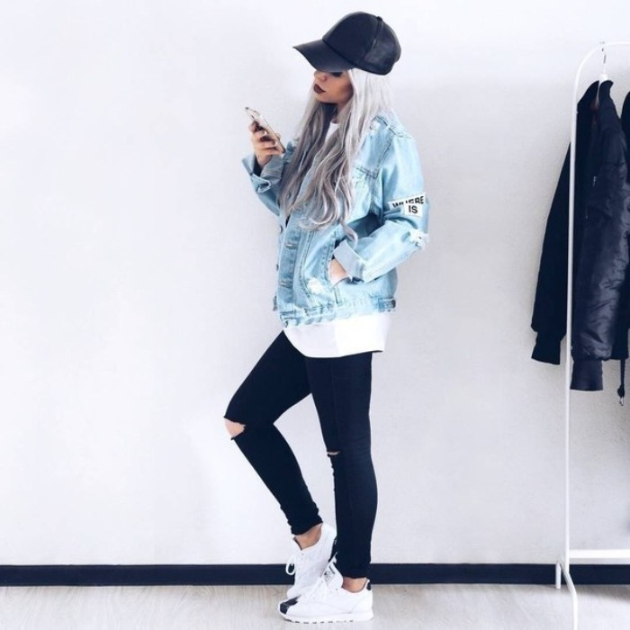 platinum blonde young woman, with long wavy hair, and a black baseball cap, holding a mobile phone, dressed in 90s grunge clothing, ripped black skinny jeans, white oversized t-shirt, and pale blue denim jacket, with a few patches