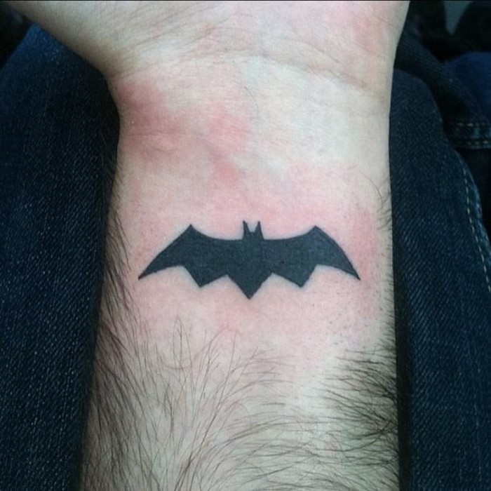 sign of batman, tattooed in solid black, on a man's wrist, lower arm tattoos, simple shape of a bat in flight