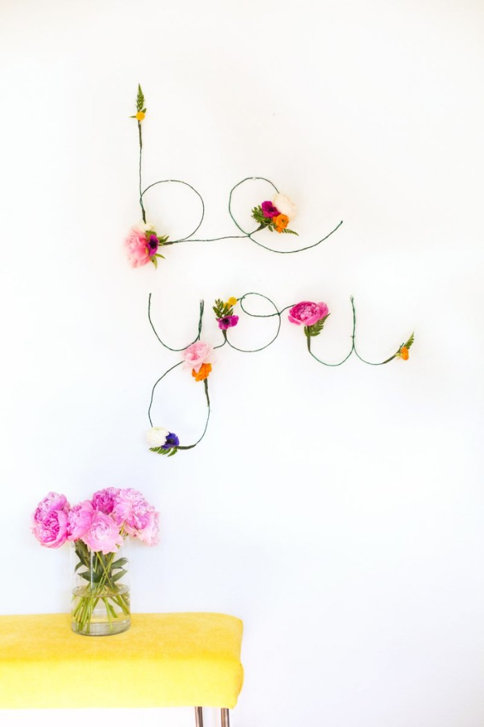 the words be you, created from green wire, and decorated with pale pink, purple and yellow faux flowers, diys for girls, mounted on a white wall, near a yellow table, with a vase, containing pink flowers