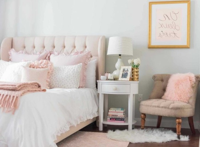 powder pink soft headboard, on a bed with white bedding, and pale pink cushions, room with light grey walls, beige vintage chair, and a white bedside table