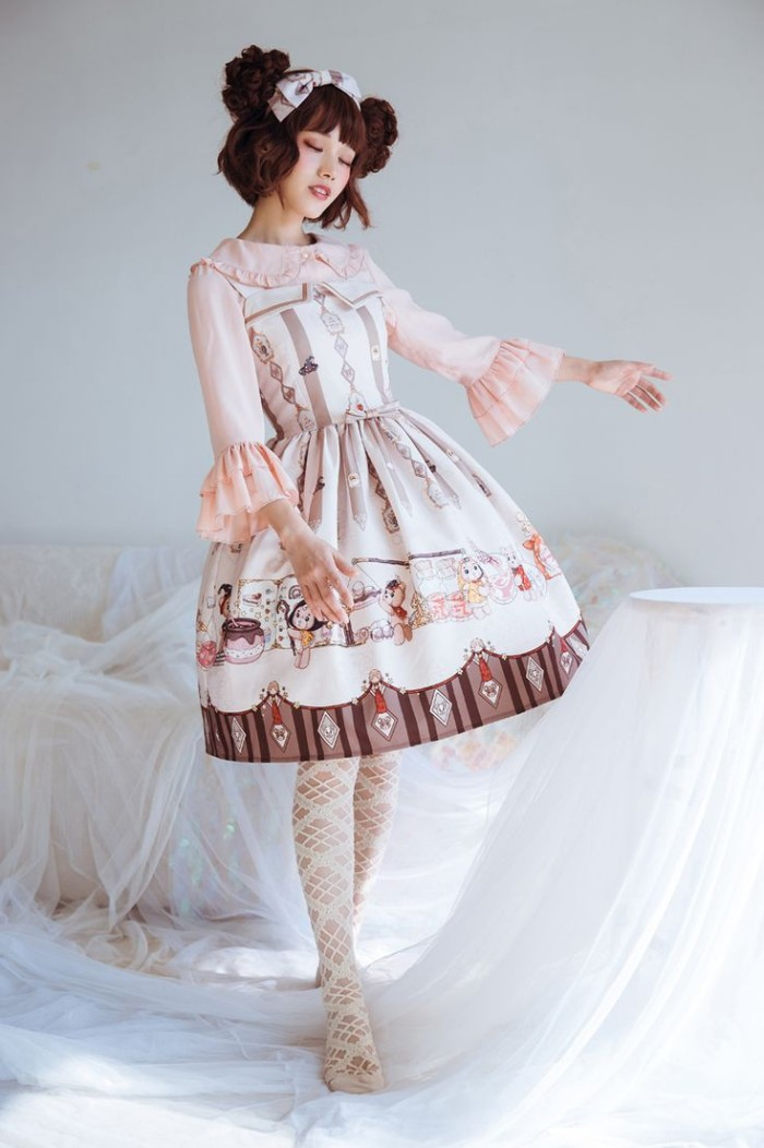 lolita fashion, off-white dress, with beige and brown motifs, worn over a pale pink shirt, with frilly sleeves, by a pale slim woman, in a brunette wig, featuring side buns