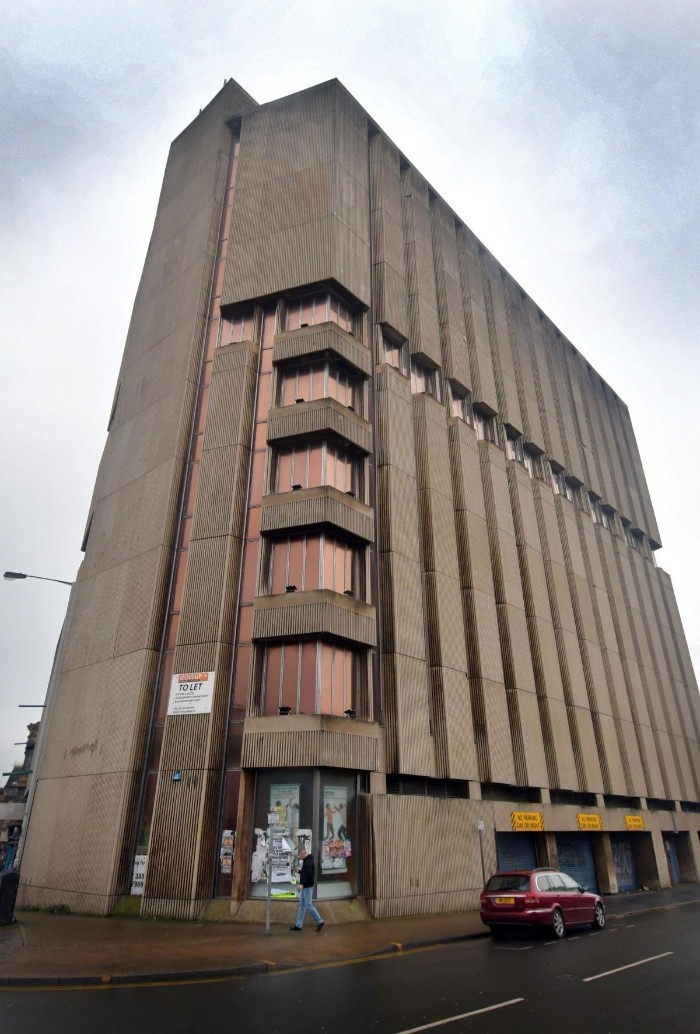 high point building, in bradford england, old beige concrete structure, with brown reflective wondows