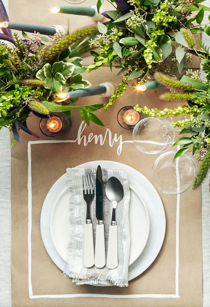 thanksgiving table setting, beige paper place mat, featuring the name henry, written in white, plates and cutlery, glasses and lit candles, three bouquets with green plants