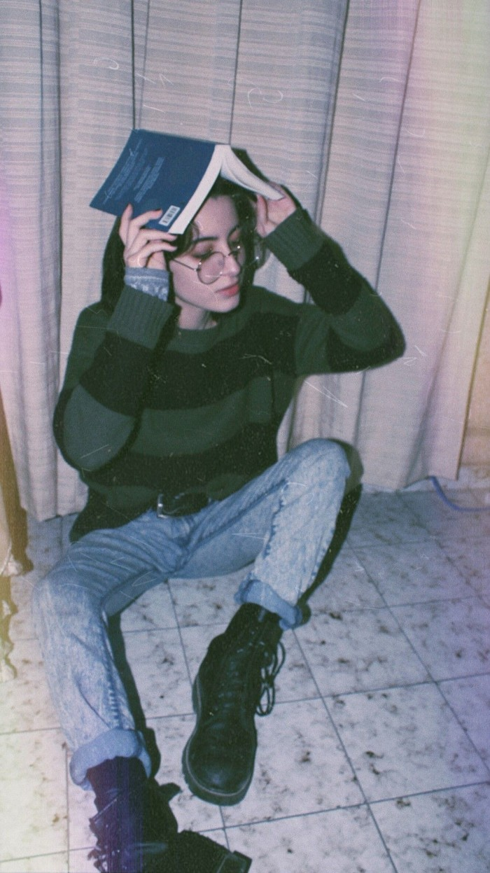 pale young woman, holding an open book over her head, dressed in pale blue, acid wash jeans, and a jumper with large black, and dark green stripes, 80s grunge, black leather lace up combat boots