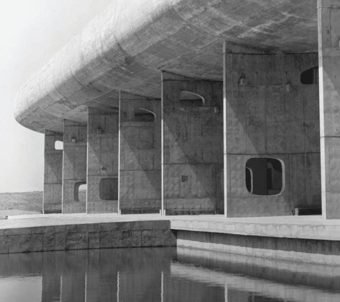 assembly building in chandigarh india, designed by le corbusier, oval concrete segment, propped up by several large concrete walls, featuring holes in different shapes