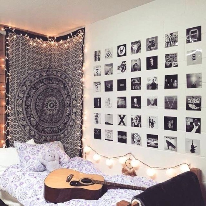 acoustic guitar laying on a bed, with white and blue bedding, teenage bedroom ideas for small rooms, walls decorated with black and white photos, and a fabric wall hanging, surrounded by lit fairy lights
