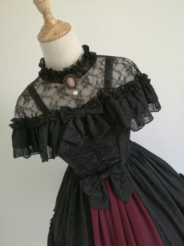 lolita style dress, made from black lace, with a purple detail, two bows and a cameo brooch, on a mannequin