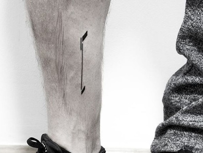 half of an arrow, simple and minimalistic design, tattooed in black ink, on a person's lower leg, meaningful tattoo ideas, symbolizing a fresh start, looking at the future