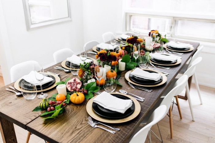 thanksgiving dinnerware, long wooden rectangular table, set for eight people, pale beige and black plates, glasses and silver cutlery, decorative pumpkins, leaves and fruit