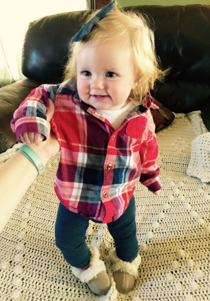 laughing one-year-old with short blonde hair, wearing dark blue skinny jeans, and a plaid shirt in red, white and dark grey, baby girl thanksgiving outfit, dark blue bow, on top of her head