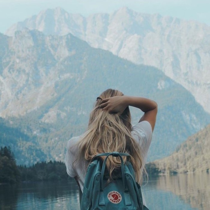 woman wearing a white t-shirt, and a teal blue backpack, running a hand through her blonde hair, while looking at a lake near a mountain, 90s grunge fashion