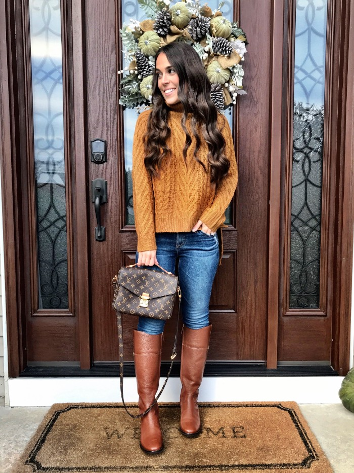 cable knit jumper in orange, worn with blue skinny jeans, and tall brown leather boots, by a smiling brunette woman, holding a designer bag,thanksgiving outfits for women