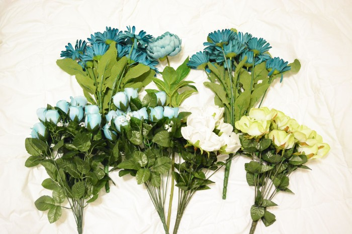 six bouquets of faux flowers, in pale blue and teal, white and pale yellow, diys for your room, placed on a white fabric