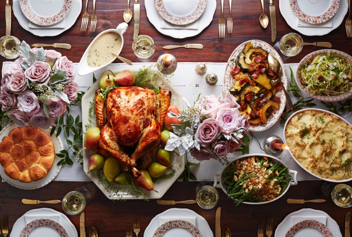 pale pink roses, in two small bouquets, placed on a table, featuring a roasted turkey, mashed potato and other dishes, thanksgiving text messages, plates and cutlery for six people