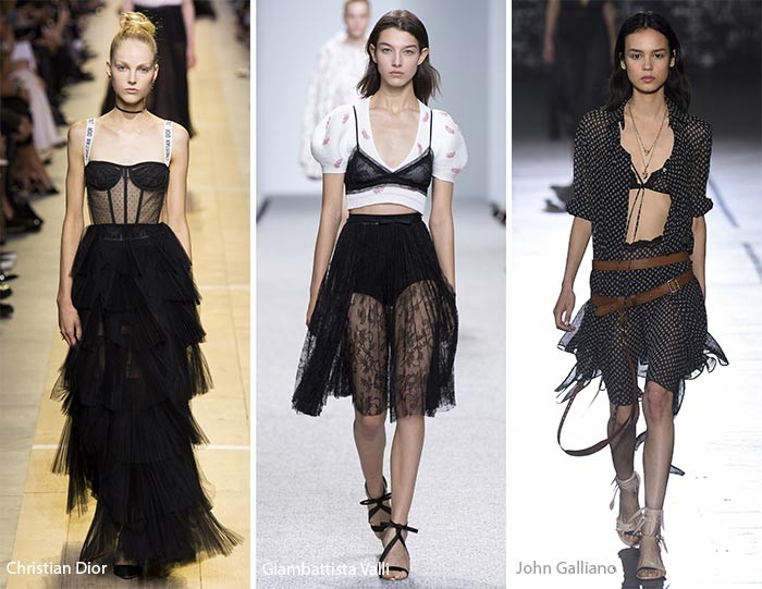 models on a catwalk, wearing black lace bralettes, with a black frilled maxi skirt, a sheer embroidered, black knee-length skirt, and a two piece suit