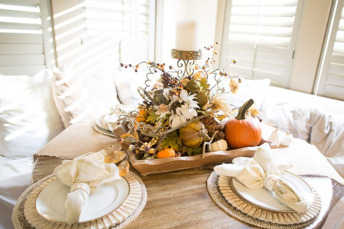 very bright room, with white window shutters, and a white sofa, near a small pale beige, round wooden table, set for two, and decorated with a centerpiece, featuring small pumpkins, gourds and leaves, berries and white flowers