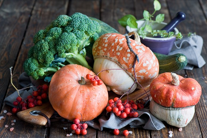 berries on small thin branches, several pumpkins in strange shapes, broccoli and a gourd, happy thanksgiving wishes, mortar and pestle with herbs nearby