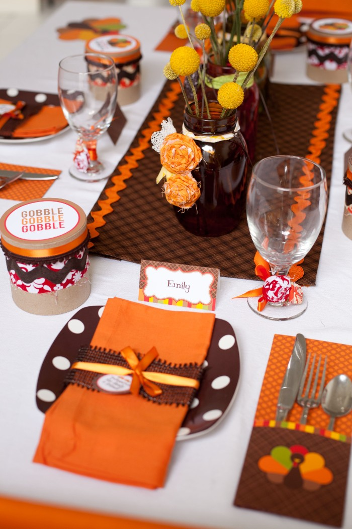 orange and brown plates, napkins and tablecloth, on a white table, decorated by a dark brown vase, containg yellow flowers, thanksgiving table setting, for the children's table