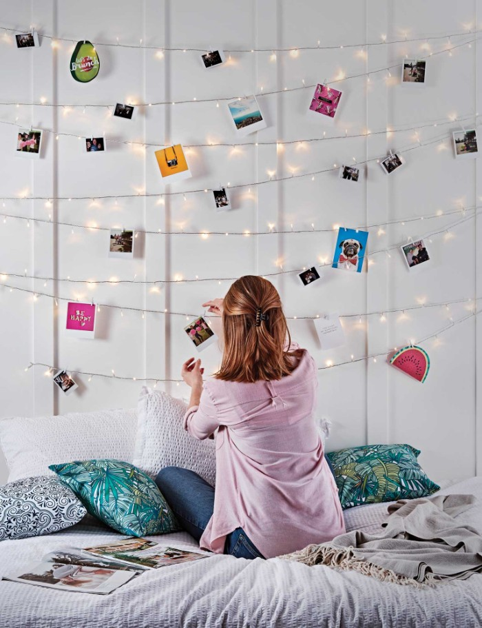 cheap ways to decorate a teenage girl's bedroom, slim brunette woman, hanging a photo on a string of fairy lights, using a small clothes peg, more lit string lights overhead