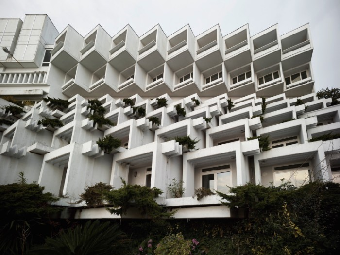 croatian hotel in opatija, made from multiple, white cube-like shapes, decorated with various green plants