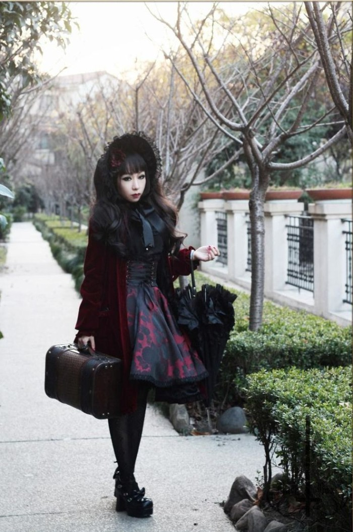 parasol in black, and a coffer bag, carried by a gothic style lolita, with a black lace bonnet, dressed in a wine red velvet coat, over a black and red dress, featuring a corset